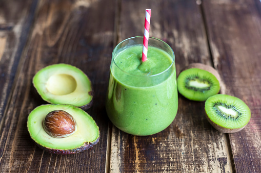 Kiwi「Glass of avocado kiwi smoothie and sliced fruits on wood」:スマホ壁紙(10)