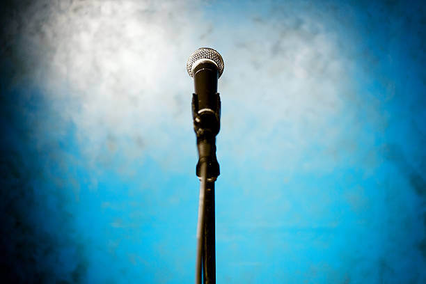 Microphone on stage with blue background:スマホ壁紙(壁紙.com)