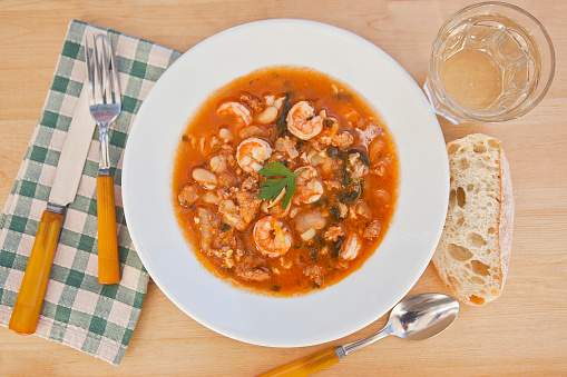 Andouille「Bowl of shrimp gumbo with parsley garnish on a wood table with a glass of white wine, crusty bread, napkin and eating utensils」:スマホ壁紙(2)