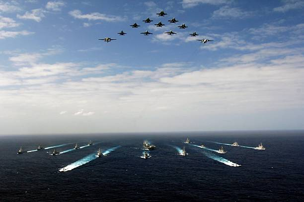 Pacific Ocean (November 14, 2006) - Aircraft assigned to Carrier Air Wing Five (CVW-5) fly over a group of 18 U.S. and Japanese Maritime Self-Defense Force ships, at the conclusion the two nations' exercise ANNUALEX.:スマホ壁紙(壁紙.com)
