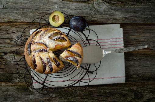 スモモ「Homemade prune cake with cooling rack and cake server on wooden table, close up」:スマホ壁紙(18)
