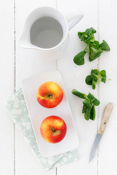 Empty jar, bowl with two apples kitchen knife and lamb's lettuce on white wooden table, elevated view:スマホ壁紙(壁紙.com)