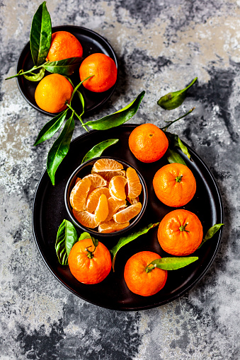 Tangerine「Tangerines with leaves, on plate and pieces in bowl」:スマホ壁紙(0)