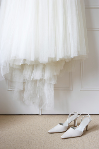結婚「White shoes on floor beneath wedding dress hanging outside wardrobe」:スマホ壁紙(4)