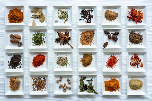 Fennel「Variety of colorful, organic, dried, vibrant Indian food spices in white ceramic dishes on a white wood grain style table background.」:スマホ壁紙(6)