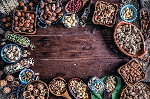 Pine Nut「Variety of dried fruit and nuts on a table in a old fashioned rustic kitchen making a frame with copy space」:スマホ壁紙(16)