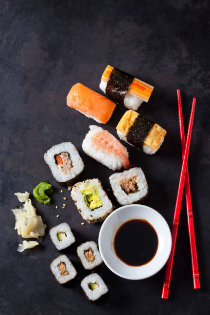 Variety of sushi with wasabi, ginger and bowl of soy sauce on dark ground:スマホ壁紙(壁紙.com)