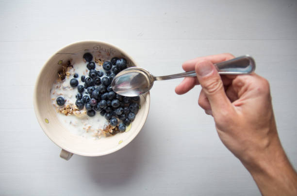 Hand with spoon reaching for breakfast cereal with blueberries and milk:スマホ壁紙(壁紙.com)