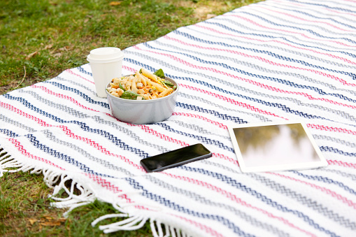 Portability「Cell phone, tablet, coffee to go and a bowl of noodle salad on blanket in a park」:スマホ壁紙(1)