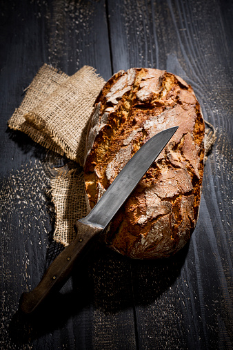 Loaf of Bread「Crusty bread and knife on jute in front of dark background, elevated view」:スマホ壁紙(14)