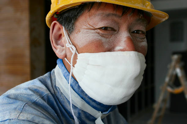A worker wearing a cotton mask pauses from work sanding ceiling plaster in a new office tower in Beijing.:ニュース(壁紙.com)