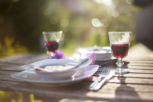 Laid garden table with two glasses of red wine at backlight:スマホ壁紙(壁紙.com)