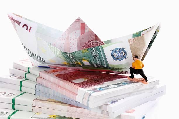 Figurine on bundles of euro notes with paper boat:スマホ壁紙(壁紙.com)