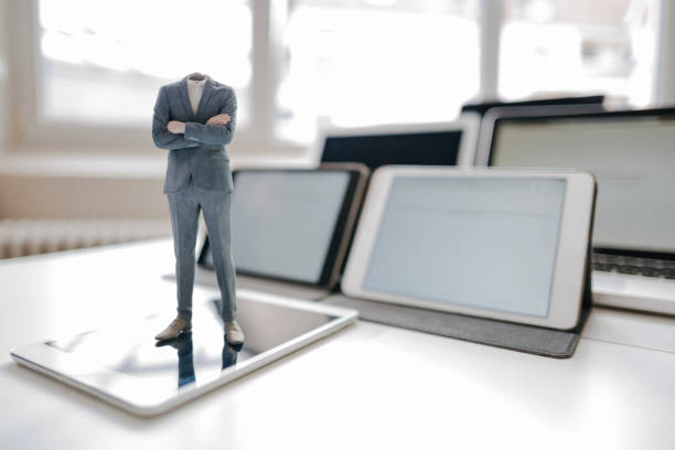 Headless businessman figurine standing on digital tablet on a desk:スマホ壁紙(壁紙.com)