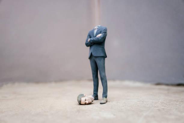Headless businessman figurine standing on cocrete:スマホ壁紙(壁紙.com)