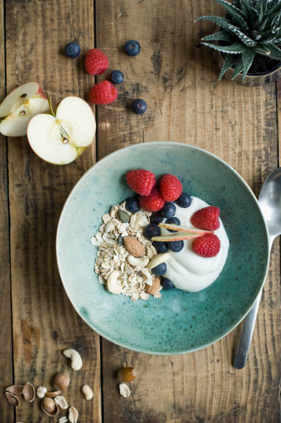 Breakfast bowl with granola, yogurt, nuts, apple, raspberry, blueberry on wood:スマホ壁紙(壁紙.com)