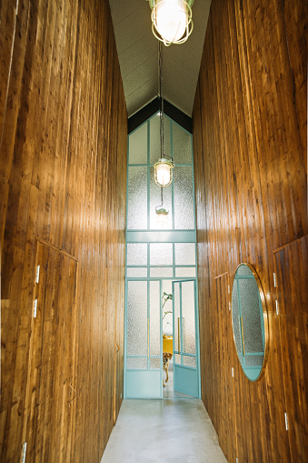 Hotel Reception「Hallway of a hotel like setting a high ceiling and with barn-wood and blue pastel steel doors giving view on the interior living room or lobby.」:スマホ壁紙(16)