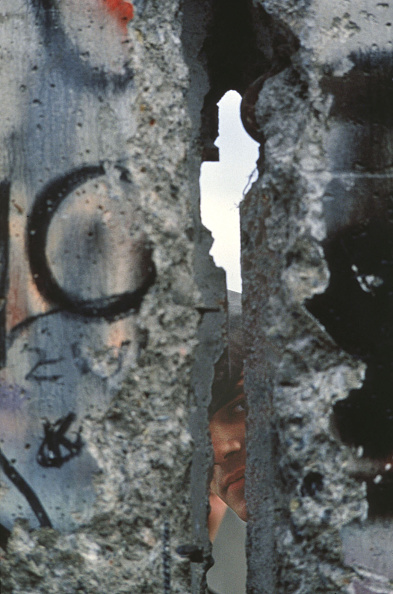 Collapsing「An East German Border Guard Peers Through A Broken Piece Of The Berlin Wall During The C...」:写真・画像(17)[壁紙.com]
