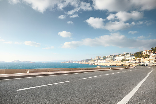 Motor Vehicle「Empty curved road with background sea and city」:スマホ壁紙(9)