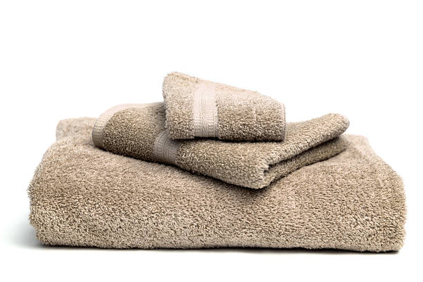 A pile of brown bath towels on a white background:スマホ壁紙(壁紙.com)