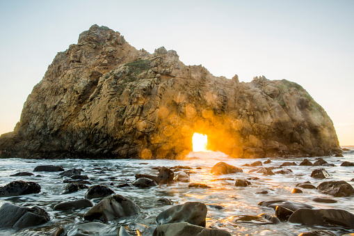 カラフル「Sun shining through rock formation to ocean waves, Big Sur, California, United States」:スマホ壁紙(10)