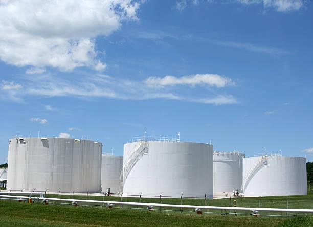 Several white storage tanks in a grassy field:スマホ壁紙(壁紙.com)