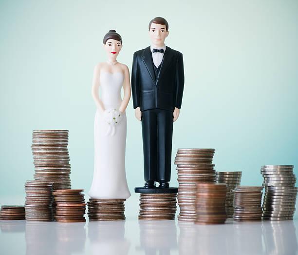 Close up of wedding cake figurines on stacks of coins:スマホ壁紙(壁紙.com)