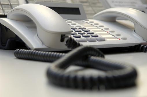 Focus On Background「Close up of white landline phone on desk」:スマホ壁紙(1)