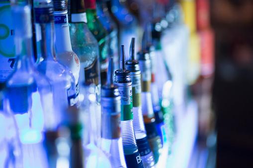 Drinking「Close up of liquor bottles illuminated at bar」:スマホ壁紙(2)