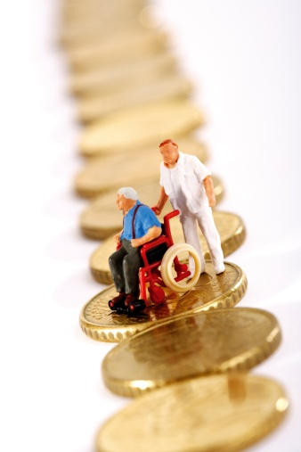 A Helping Hand「Figurine in wheelchair and caregiver on row of coins」:スマホ壁紙(2)