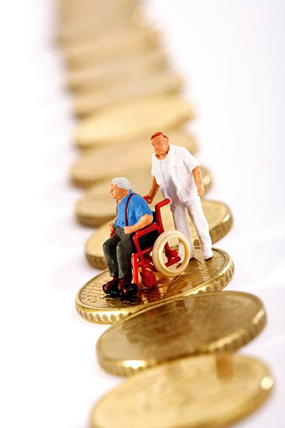 Figurine in wheelchair and caregiver on row of coins:スマホ壁紙(壁紙.com)