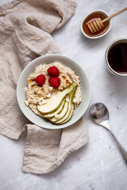 oatmeal with raspberries and pear in a rustic plate on a marble table. Morning concept with copy space:スマホ壁紙(壁紙.com)