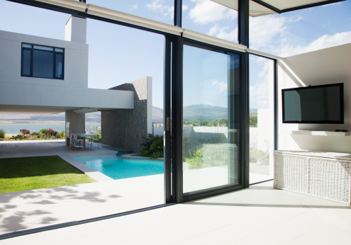 South Africa「View of patio and swimming pool through sliding doors of modern house」:スマホ壁紙(3)