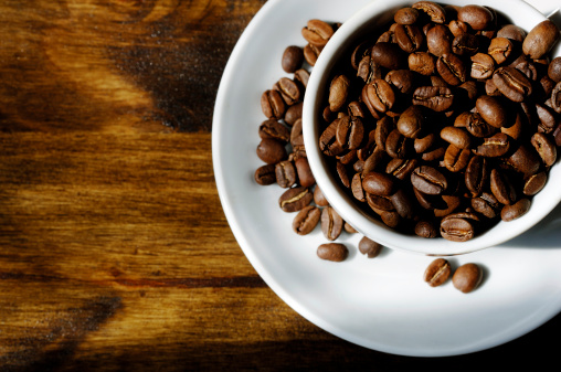 Legume Family「cup filled with roasted coffee beans on oak table」:スマホ壁紙(1)