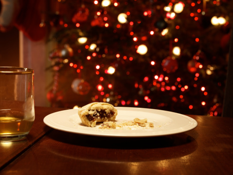 Christmas Decoration「Half eaten mince pie on empty plate, Christmas tree behind」:スマホ壁紙(7)