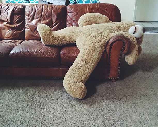 Stuffed teddy bear laying on couch:スマホ壁紙(壁紙.com)