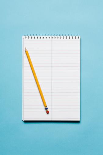 カラー背景「Single yellow sharpened pencil with blank stenographer notebook on blue background」:スマホ壁紙(9)