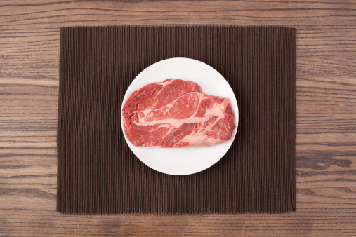 Plate「A raw steak on a plate on a wood table」:スマホ壁紙(0)