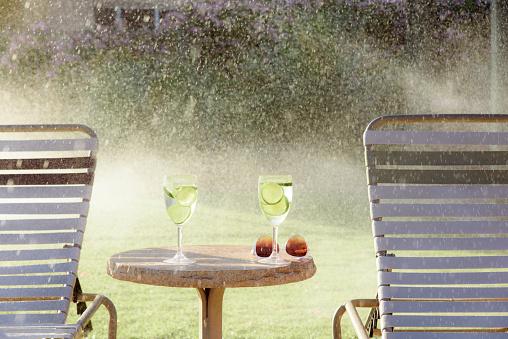 雨「Water spraying on drinks and lounge chairs」:スマホ壁紙(19)