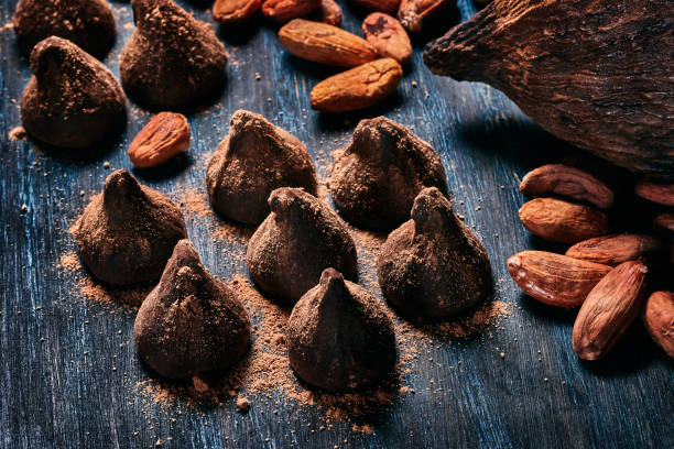 Close-up low key image of a chocolate truffe with cocoa fruit and beans. Old fashioned style on a blue rustic table:スマホ壁紙(壁紙.com)