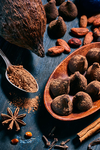 chestnut「Close-up low key image of a chocolate truffe with cocoa fruit and beans. Old fashioned style on a blue rustic table」:スマホ壁紙(2)