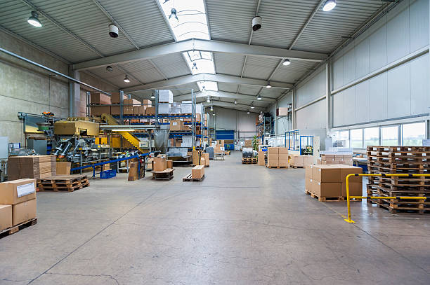Empty industrial hall with stored packages, paletts and packaging machine:スマホ壁紙(壁紙.com)