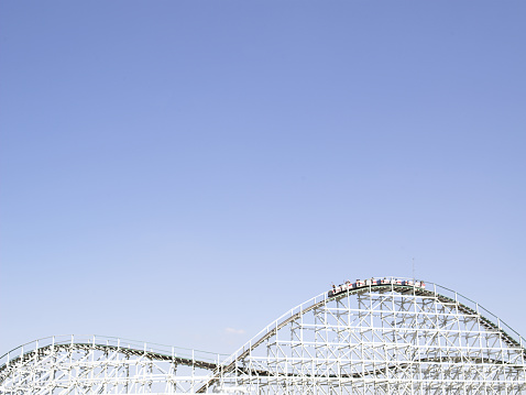 Carnival「Rollercoaster with people raising arms in air in cars on top」:スマホ壁紙(5)