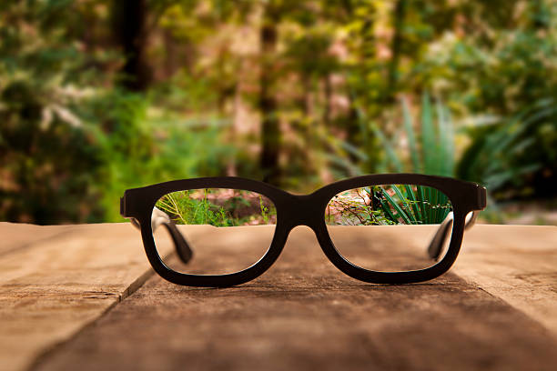 Eyeglasses on rustic wooden table. Forest background.:スマホ壁紙(壁紙.com)