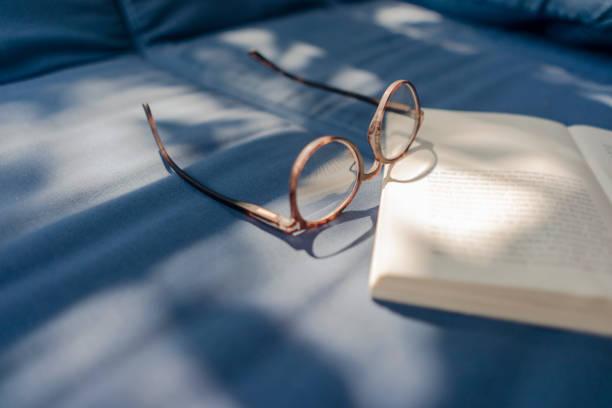 Eyeglasses and book lying on couch:スマホ壁紙(壁紙.com)