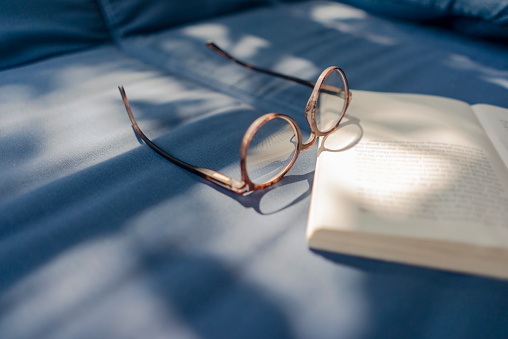 Weekend Activities「Eyeglasses and book lying on couch」:スマホ壁紙(9)