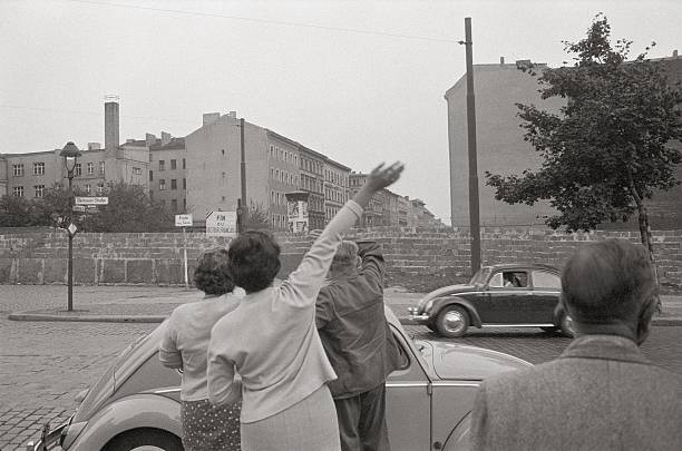 Waving people in front of the Berlin Wall:ニュース(壁紙.com)