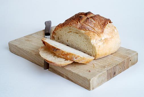 Craftsperson「Sliced Round Loaf of Bread on a Cutting Board」:スマホ壁紙(12)