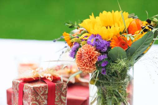 Focus On Foreground「Bunch of flowers and gift on outdoor table」:スマホ壁紙(5)