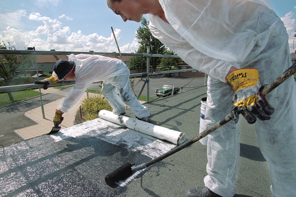 Bituminous Coal「Two workers laying bituminous roofing on a flat roof」:写真・画像(2)[壁紙.com]